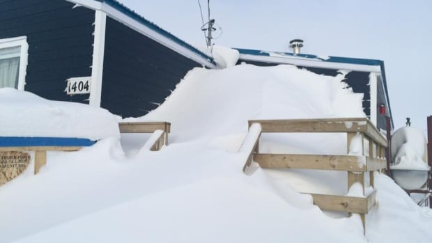 Brandon Alger's Iqaluit home sits beneath a mountain of snow after Iqaluit was hit with a 50-hour blizzard.