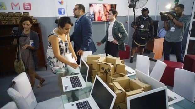 Google's head of Cuba operations, Brett Perlmutter, center right, and Alexis Leiva Machado, a Cuban sculptor known as Kcho, center left, walk inside the new Google technology centre which will offer free internet access in Havana.