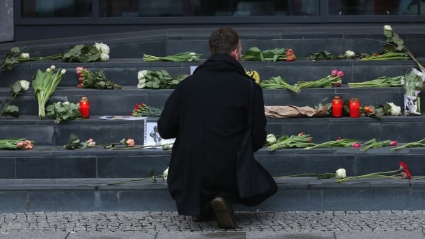 BERLIN, GERMANY - MARCH 22:  A man lays flowers at the steps of the Belgian Embassy following today's terrorist attacks in Brussels on March 22, 2016 in Berlin, Germany. The Islamic State has claimed responsibility for the attack in which terrorists detonated three explosives devices at Brussels airport and in a metro train and killed at least 30 people.  (Sean Gallup/Getty)