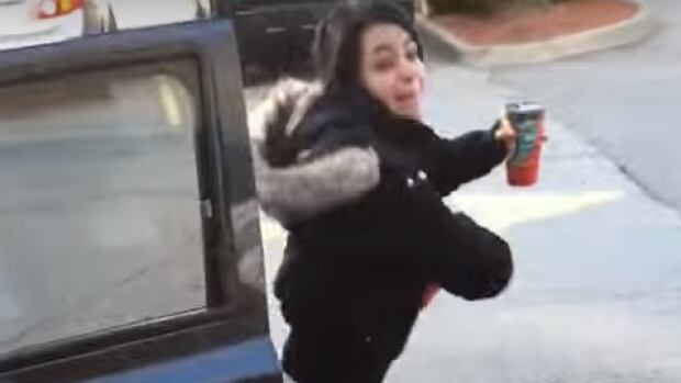 A woman who tossed two cups of coffee at a man when he confronted her for parking in a disabled parking spot outside a Tim Hortons has received a police warning after a video of the incident garnered international attention. She has not been named.