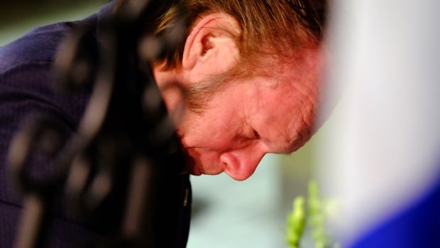 Kenny Neville, who identified himself as being a proud member of Ford Nation, cries as he signs a book of condolences for Rob Ford's family at city hall on Tuesday.