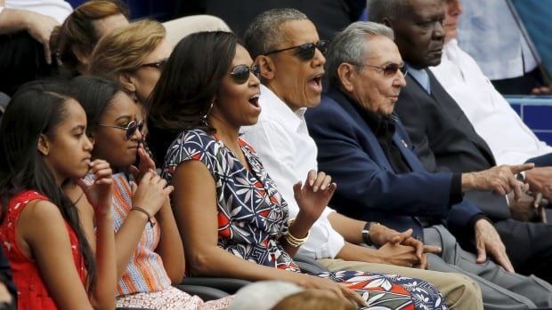 U.S. President Barack Obama and his family react along with Cuban President Raul Castro to an exhibition baseball game between the Cuban National team and the MLB Tampa Bay Rays at Estadio Latinoamericano in Havana on Tuesday.