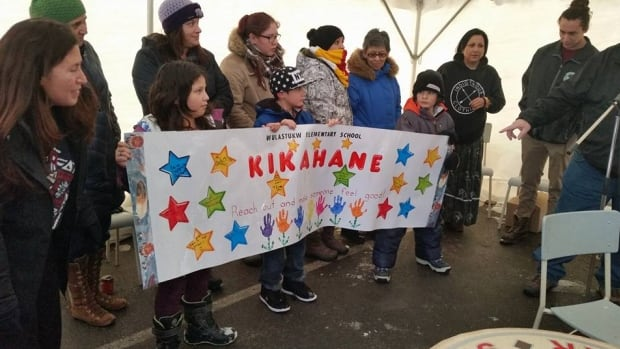 Students at Kingsclear Elementary School present a banner to the community during its week of healing.