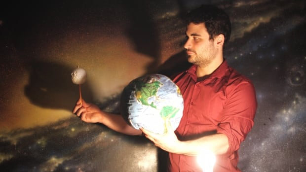 H.R. MacMillan astronomer Derek Kief uses models to demonstrate how a penumbral lunar eclipse occurs. The moon is covered by the edge of the earth's shadow.