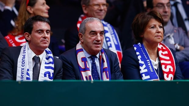 """France Prime Minister Manuel Valls, left, is seen here attending a 2014 Davis Cup match with French Federation President Jean Gachassin, centre. Valls said Wednesday that major sporting events like the Euro 2016 soccer tournament and the Tour de France will show that """"we're not scared, that we know we're facing up to a terrorist threat"""" in the wake of the attacks on Brussels."""