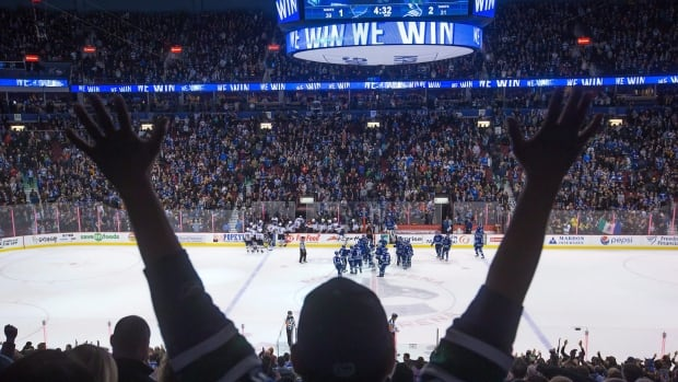 Better days: A fan cheers as the Canucks beat St. Louis in an overtime shootout during an NHL hockey game in Vancouver on March 1, 2015, a season which ended in a playoff berth.  This season, the Canucks are in a slump.
