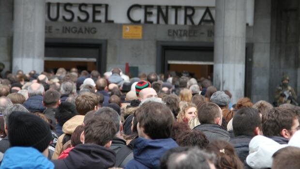 People wait to have their bags searched before entering the central train station in Brussels on Thursday, as part of strict security measures in the city in the wake of the airport and subway bombings.