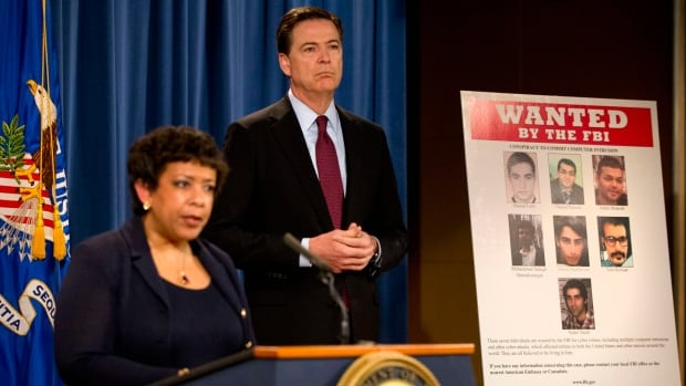 Attorney General Loretta Lynch and FBI Director James Comey stand by a wanted poster of seven hackers tied to the Iranian government who were charged Thursday in a series of punishing cyberattacks on a small dam outside New York City and on dozens of banks.
