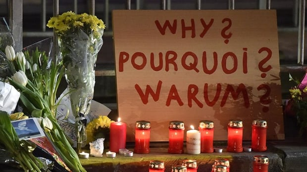 """A sign reads """"Why?"""" in English, French and Flemish behind candles and flowers near the Maelbeek metro station, in Brussels on Wednesday evening, March 23, 2016. Bombs exploded Tuesday at Brussels airport and one of the city's metro stations, killing and wounding scores of people, as a European capital was again locked down amid heightened security threats. (AP Photo/Martin Meissner)"""