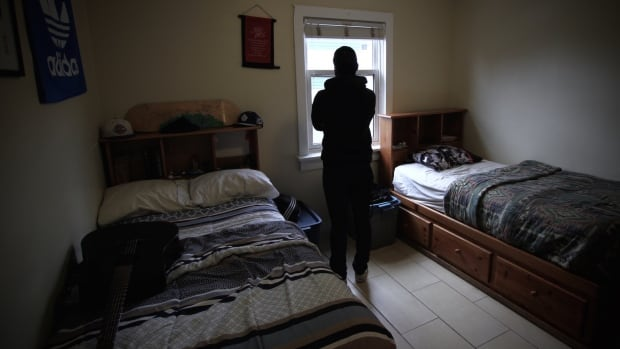 One of Last Door's clients, a 19-year-old recovering from heroin addiction, looks out a window in one of the bedrooms at the youth residence in New Westminster.