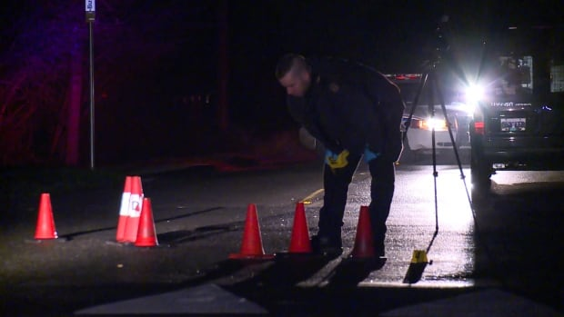 A Surrey RCMP officer lays evidence markers at the scene of a shooting in Panorama Ridge.