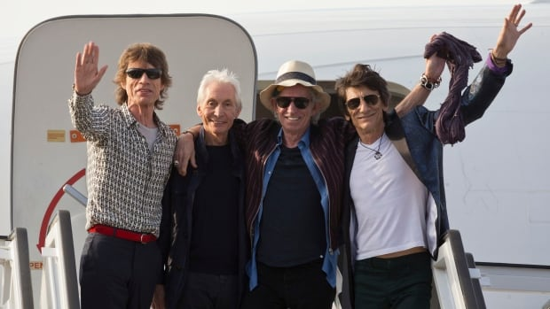 Members of the Rolling Stones, from left, Mick Jagger, Charlie Watts, Keith Richards and Ron Wood, pose for photos from the plane that brought them to Cuba at Jose Marti international airport in Havana on Thursday.