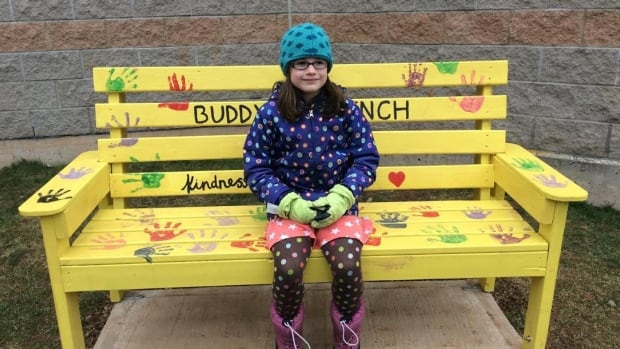 Grade 2 student Evie Hall checks out on of the new benches installed on her school's playground. They are intended to be a spot children can go when they want some company.