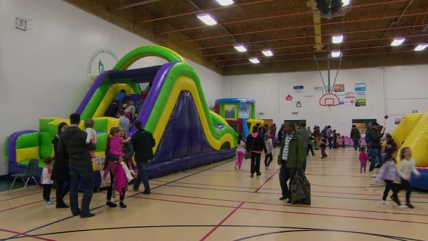 Children play in one of several inflatable bouncy structures set up at a family party at Greendell Park Community Centre in Winnipeg on Friday.