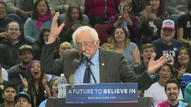 Democratic presidential hopeful Bernie Sanders reacts as a bird he had just noticed on the ground suddenly landed in front of him during a rally in Portland, Oregon on Friday.