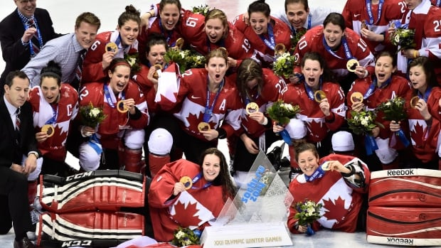 Canadian players pose for a team photo after beating the United States 3-2 in overtime in the women's hockey final at the 2014 Sochi Winter Olympics.