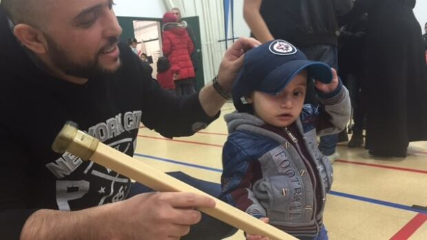 Jarah Najim, right, who is one and a half years old, dons a Winnipeg Jets hat and holds a hockey stick during a community party at the Greendell Park Community Centre on Saturday.
