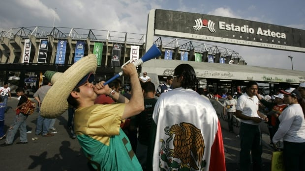 In this Oct. 2, 2005 file photo, a fan wearing a sombrero blows a horn outside of the Azteca Stadium in Mexico City, Mexico.