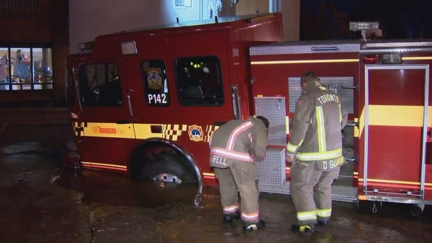 A Toronto fire truck is stuck in a sinkhole caused by a water main break, early on Sunday morning.
