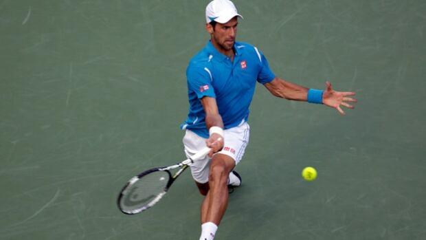 Novak Djokovic returns to Joao Sousa during their match at the Miami Open tennis tournament on Sunday in Key Biscayne, Fla.