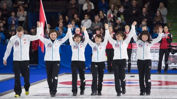 Team Japan celebrate their silver medal after losing to Switzerland following the gold medal game at the women's world curling championship in Swift Current, Sask. Sunday, March 27, 2016.