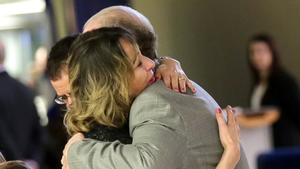 Renata Ford, wife of former Toronto mayor Rob Ford, hugs a well wisher at city hall where her husband lies in repose.