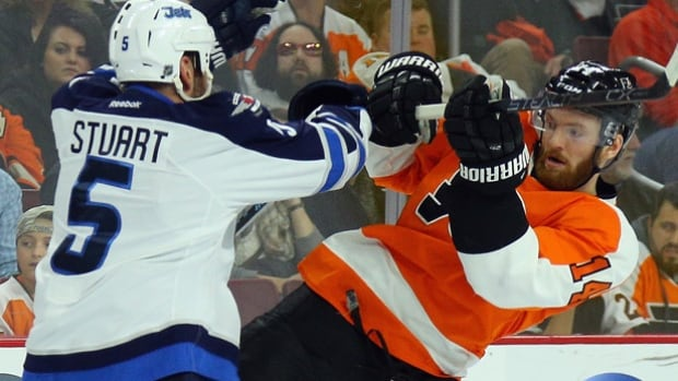 Winnipeg Jets Mark Stuart, left, exchanges pleasantries with the Flyers' Sean Couturier during the their meeting in Philadelphia. The Flyers won 3-2 in overtime on Claude Giroux's goal.