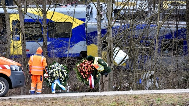 Wreaths are placed in front of two crashed trains near Bad Aibling in southwestern Germany on Feb. 10. Eleven people were killed and dozens injured when two passenger trains collided head-on at high speed in the remote countryside in southern Germany.