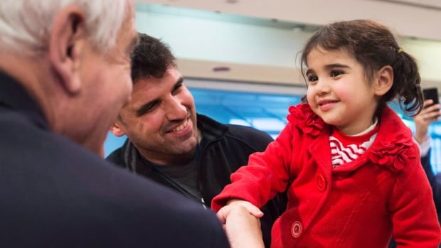 Immigration Minister John McCallum, left, meets Syrian refugee Minisa, 2, and her father Yousef, at Toronto's Pearson airport last month. The federal government has scaled back its resettlement efforts after it reach goal of 25,000, a move that has some Canadian sponsors upset with delays in welcoming more refugees.