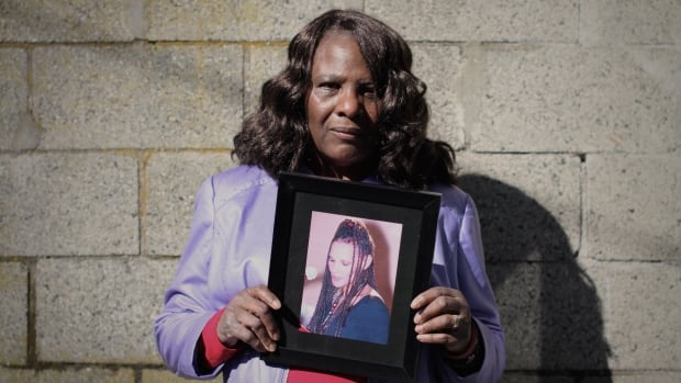 Loretta Sundstrom holds a photo of her daugther, Anita Hauck, who died after getting trapped inside a clothing donation bin.