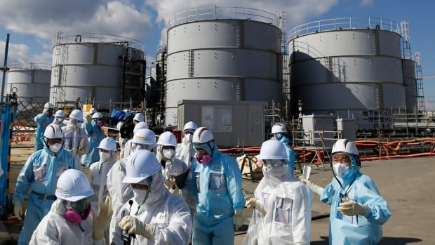 Members of the media, wearing protective suits and masks, walk in front of storage tanks for radioactive water at TEPCO's tsunami-crippled Fukushima Daiichi nuclear power plant on Feb. 10, 2016.  Nearly 800,000 tonnes of radioactive water is stored in 1,000 industrial tanks at the plant, hampering decontamination of the facility.