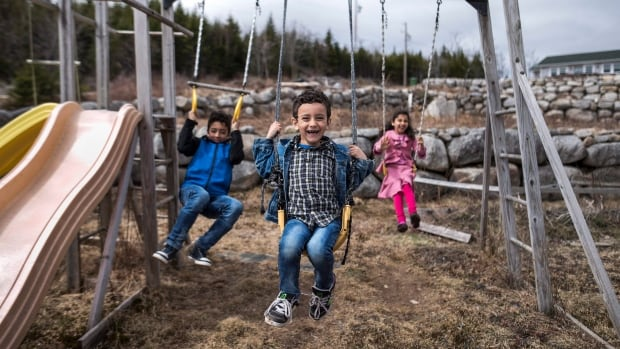 Ahmad Zeina, centre, 5, swings with his siblings Mohammad, left, 11, and Noor, 7, at the Syrian refugees' new family home in Queensland, N.S., on April 16, 2016.