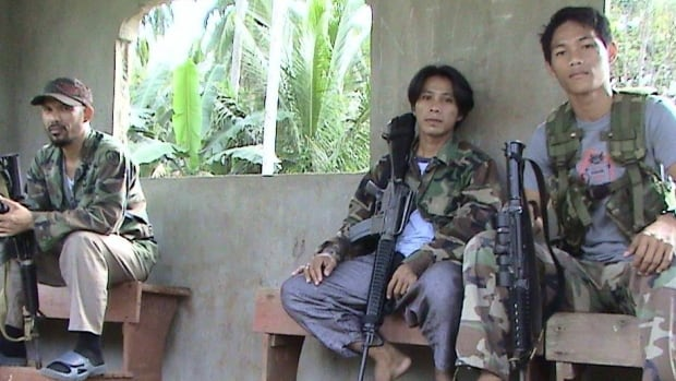 An image released by the Philippine National Police shows a top commander of the Abu Sayyaf extremist group, left, posing with comrades on Mindanao island in the southern Philippines.
