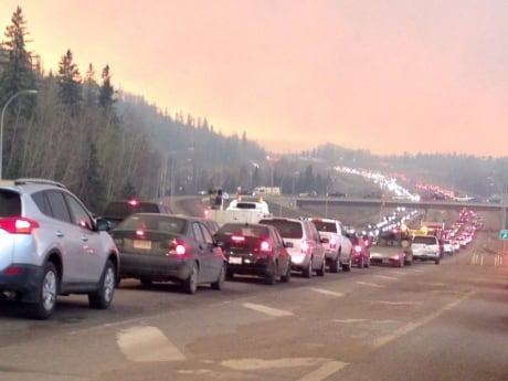 Smoke fills the air as cars line up on Highway 63, which has been breached at the MacKenzie Boulevard intersection south of the city.