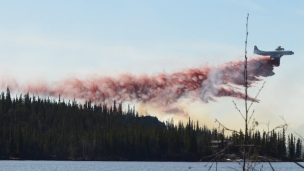 An Electra tanker plane drops red fire retardant on the Madeline Lake fire near Yellowknife on May 14. A new study says the drying of peatlands found in boreal forest is raising the risk of severe, smoky wildfires.