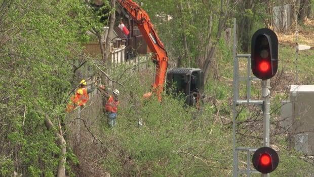 VIA Rail workers removing trees behind homes