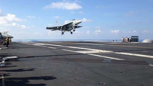 In this Friday, April 15, 2016 file photo, an FA-18 jet fighter lands on the USS John C. Stennis aircraft carrier in the South China Sea while U.S. Defense Secretary Ash Carter visited the aircraft carrier during a trip to the region.