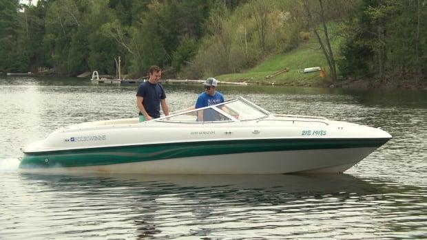 Two men take a boat ride on Lake McGregor in Val-des-Monts, Que.