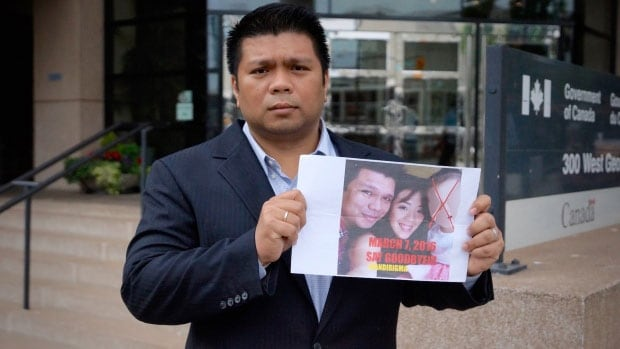 Lowell Menorca holds the image he claims a family member found on his car in the Philippines. He says the note prompted him to leave the country, and he is now seeking refugee status in Canada.