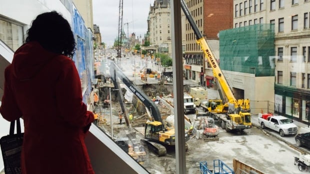 woman looks down at the sinkhole that swallowed a stretch of Rideau Street in downtown Ottawa on June 8. Rideau Transit Group said on June 20 it expects to reopen Rideau Street in a week. (Susana Mas/CBC )