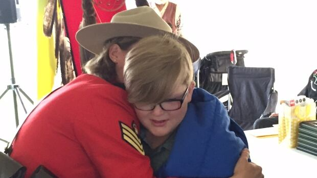 RCMP Sgt. Shannon Haggarty hugs Luca Bourdages, son of slain Mountie Marc Bourdages. Cst. Bourdages and Cst. Robin Cameron, are just two of the 71 Saskatchewan officers being honoured during the Ride to Remember.