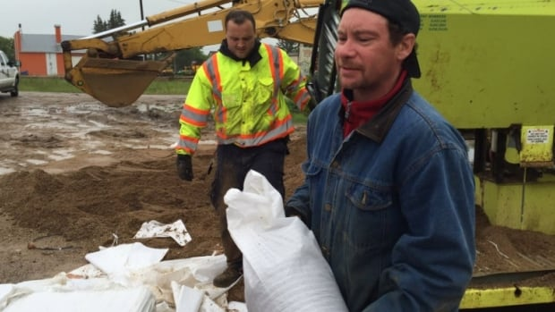 Residents in Arborfield, Sask., hurry to fill sandbags shortly after an evacuation order was given to the town Tuesday afternoon.
