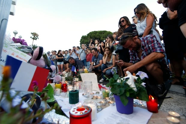 People gathered near flowers and candles left in tribute to victims after the deadly truck attack in Nice,France, which left at least 84 dead.