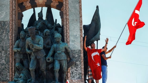 People protesting against the coup, wave a Turkish flag on top of the monument(AP Photo/Emrah Gurel)
