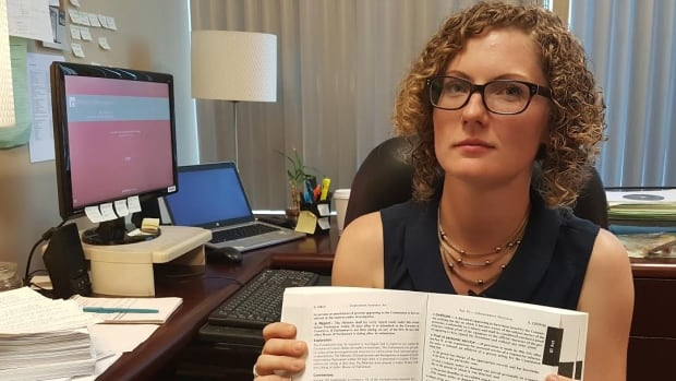 Ottawa lawyer Alison McEwen holds up a copy of the Employment Insurance Act.