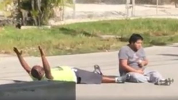 Video provided to the Miami Herald taken moments before the shooting shows Charles Kinsey lying in the middle of the street with his hands up, asking the officers not to shoot him.