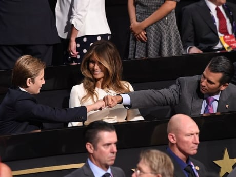 Barron Trump [L), youngest son of Republican presidential candidate Donald Trump, bumps fists with his older brother Donald Trump, Jr (R), on the final night of the Republican National Convention in Cleveland, Ohio.