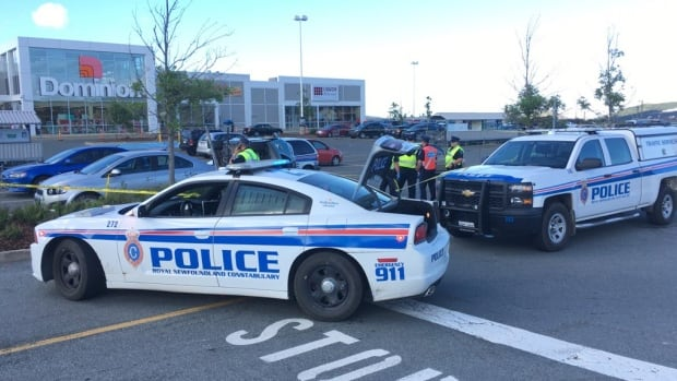 Royal Newfoundland Constabulary examine a vehicle that lies on its side after an accident Thursday afternoon on the grocery store parking lot.