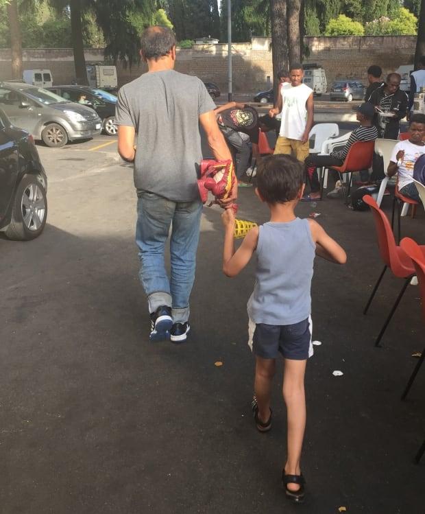 Iraqi father and son at Rome migrant centre