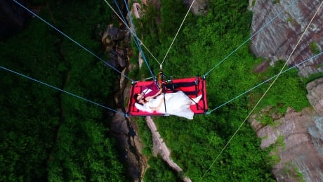 Couple exchange vows dangling 180 metres above gorge